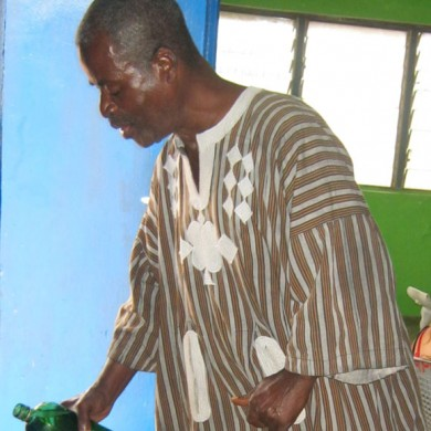 Kormantse elder pours libation invoking ancestral spirits' support for the field project